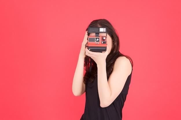 Frau machen sie ein foto mit sofortbildkamera