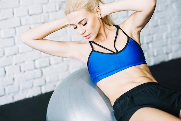 Frau macht abs übungen auf fitball