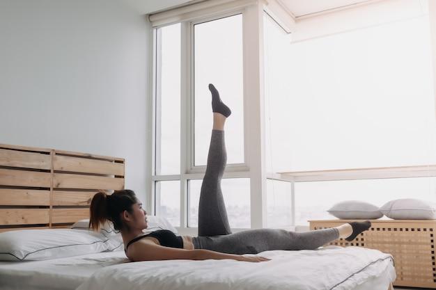 Frau macht alternatives beinheben-training in ihrer schlafzimmerwohnung