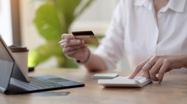 Frau macht berechnungen und kauft online mit kreditkarte ein. frau mit taschenrechner, budget und kreditpapier im büro. rechnungen, haushaltsbudget, steuern, ersparnisse, finanzen, wirtschaft, wirtschaftsprüfung, schuldenkonzept