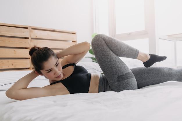 Frau macht cross-body-crunch-übungen in ihrer schlafzimmerwohnung