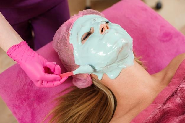 Frau macht das verfahren im schönheitssalon. alginatmaske, ultraschallreinigung. gesichtspflege. kosmetologische eingriffe ohne operation.