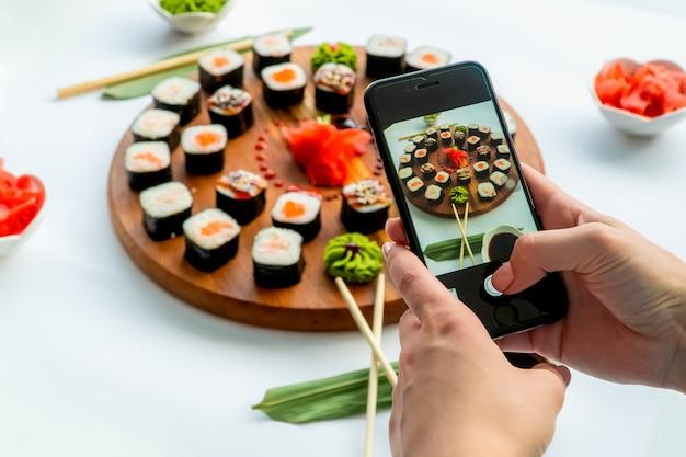 Frau macht ein bild von sushi auf einer runden holzoberfläche mit ingwer