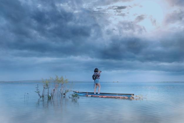 Frau macht ein foto auf dem boot im see