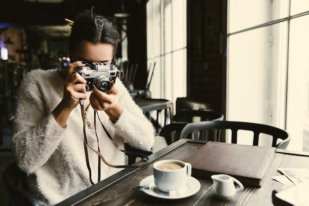 Frau macht ein foto auf dem retro- photocamera, das im café sitzt