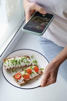Frau macht ein foto auf smartphone, hält platte mit roggen knusprigem brot mit käse und mikrogrün
