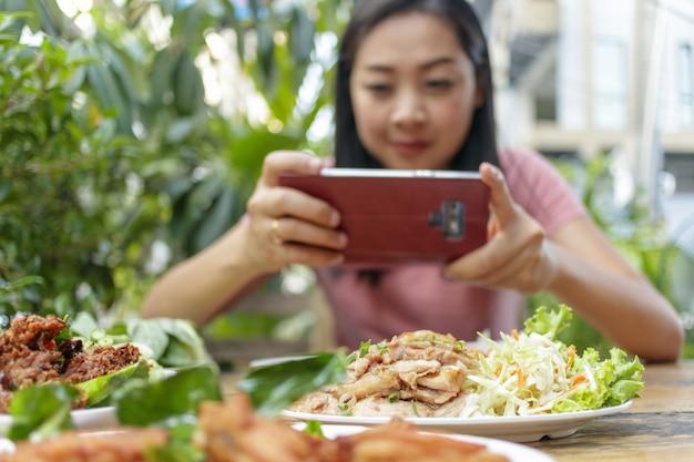 Frau macht ein foto des thailändischen lebensmittels auf dem tisch.