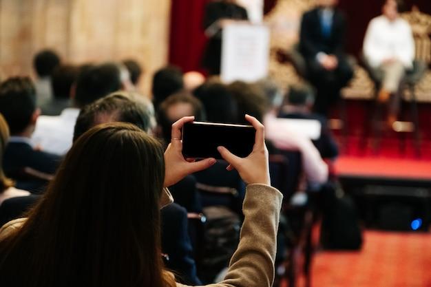 Frau macht ein foto mit einem handy in einer besprechung