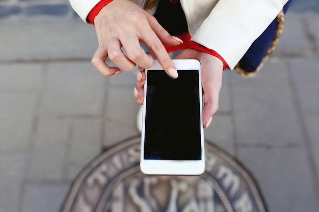 Frau macht ein foto von ihren beinen am telefon