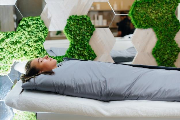 Frau macht eine kosmetologische prozedur ganzkörperverpackung in einem modernen schönheitssalon.