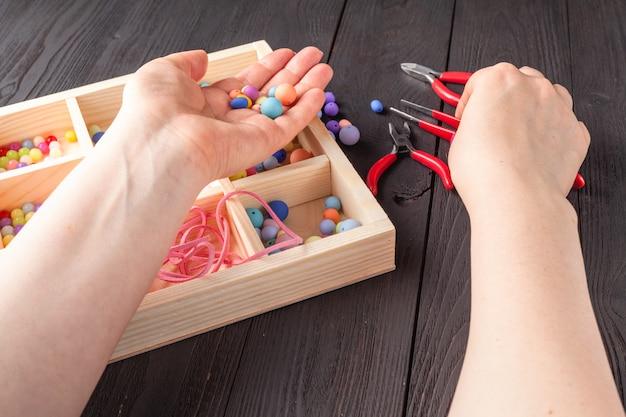 Frau macht eine verzierung aus perlen. farbperlen mischen. hobbykonzept Premium Fotos