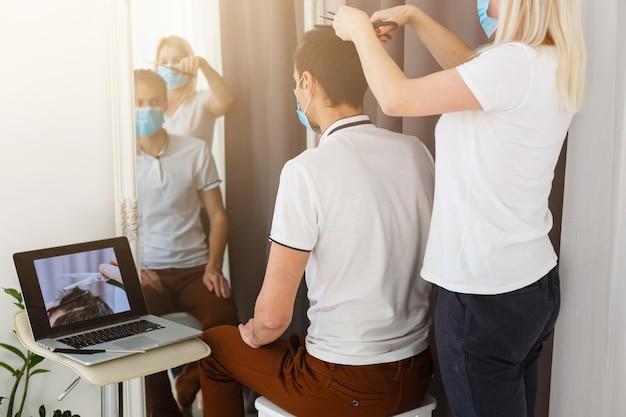 Frau macht einem mann während der quarantäne einen haarschnitt
