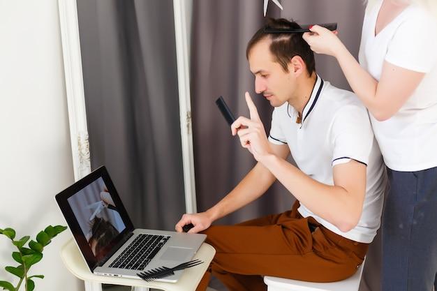 Frau macht einem mann zu hause während der quarantäne einen haarschnitt