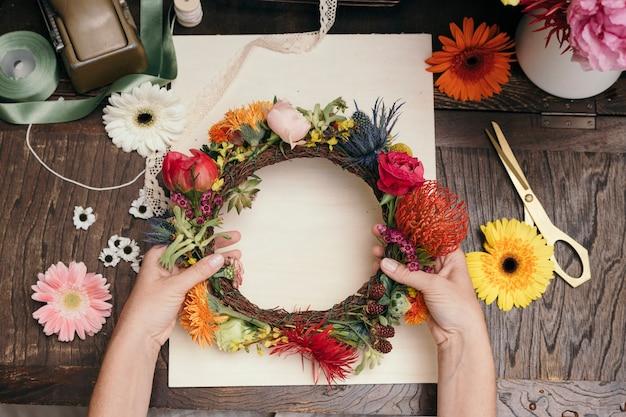 Frau macht einen floralen mittsommerkranz
