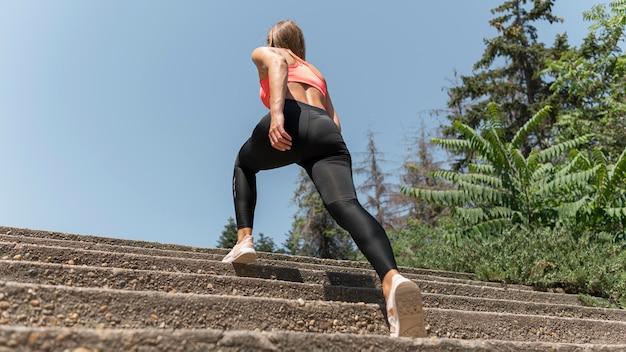 Frau macht einen großen schritt auf der treppe