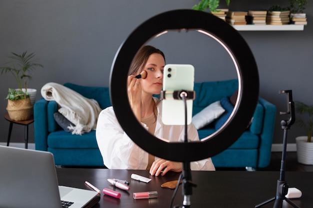 Frau macht einen make-up-vlog mit ihrem smartphone