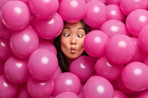 Frau macht fischlippen kreuzt die augen herum, während sie die halle mit aufgeblasenen luftballons dekoriert