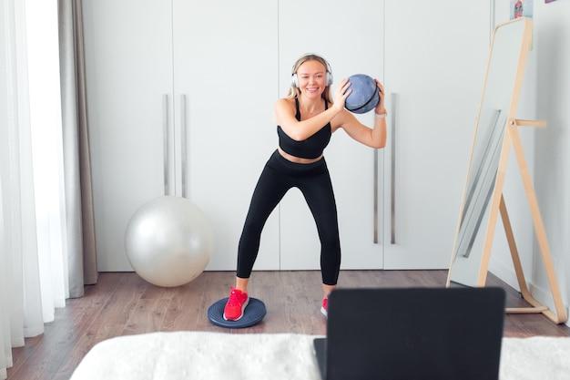 Frau macht fitnessübungen zu hause mit ball