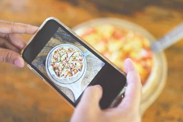 Frau macht foto von ihrer pizza mit smartphone