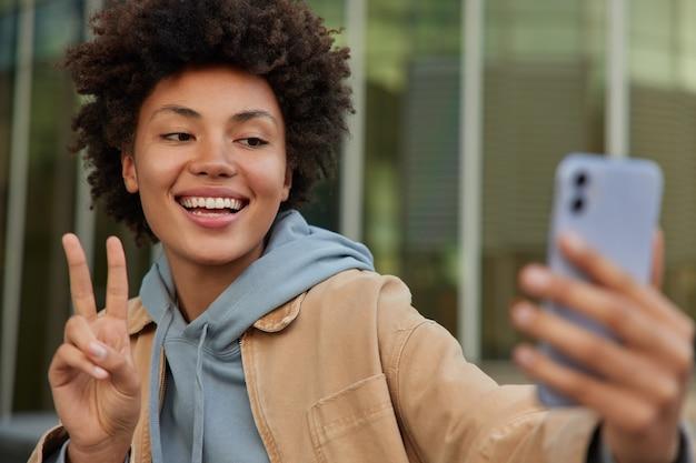 Frau macht friedensgeste macht selfie auf smartphone-kamera macht online-anruf in freizeitkleidung gekleidet und posiert im freien