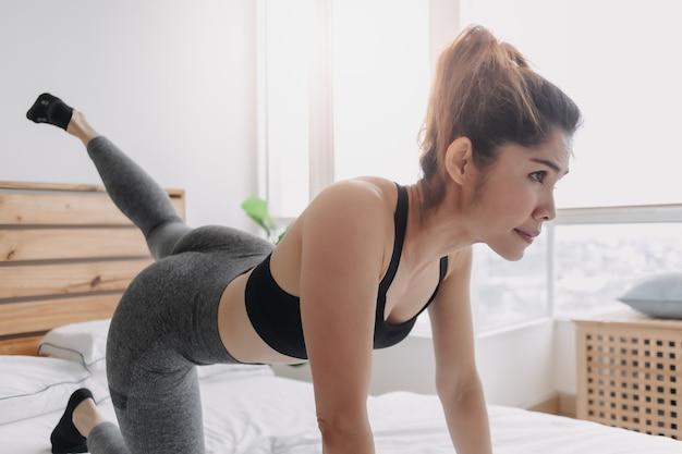 Frau macht glute-kickback-workout in ihrer schlafzimmerwohnung