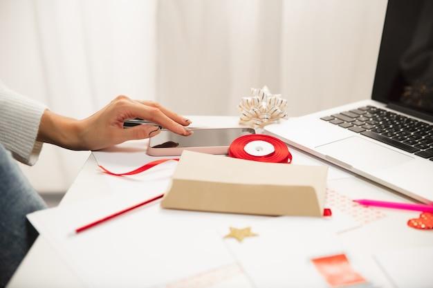 Frau macht grußkarte für neujahr und weihnachten für freunde oder familie schrottbuchung diy