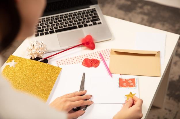 Frau macht grußkarte für neujahr und weihnachten für freunde oder familie, schrottbuchung, diy
