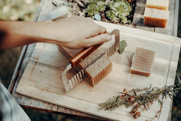 Frau macht handgemachte naturseifen auf einem alten holztisch