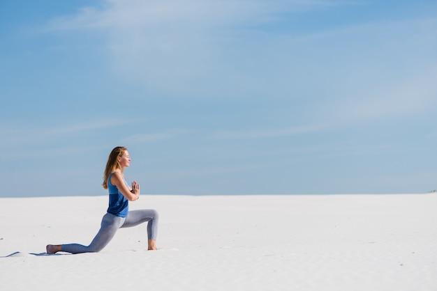 Frau macht helden yoga pose in der wüste