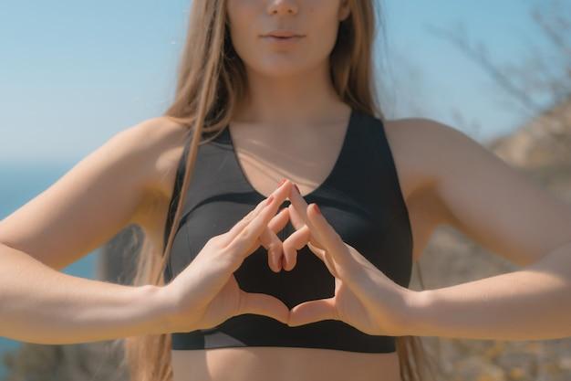 Frau macht herz mit händen am strand junge frau mit langen haaren fitnesstrainer stretching