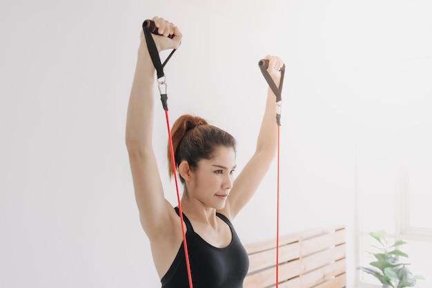 Frau macht in ihrem schlafzimmer ein widerstandsband-training für die obere brust