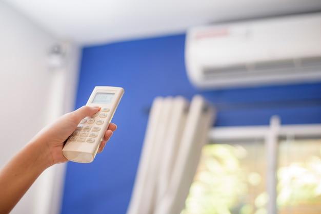 Frau macht klimaanlage in haus an