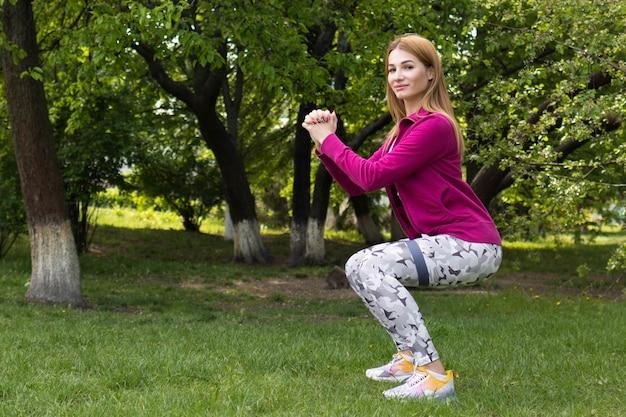 Frau macht kniebeugen für die gesundheit im park