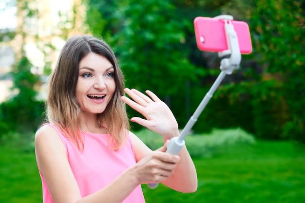Frau macht lustiges selfie und sendet videobotschaft mit lächeln für freund