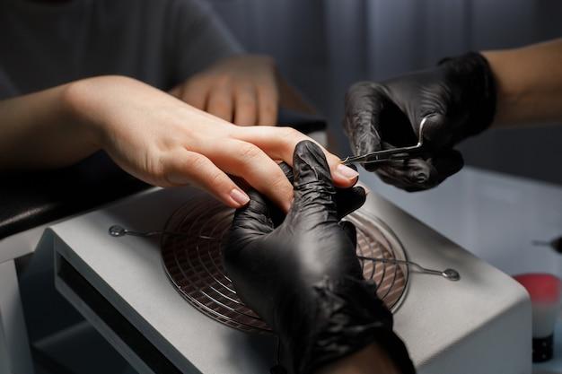 Frau macht maniküre und schneidet nagelhaut auf den nägeln aus