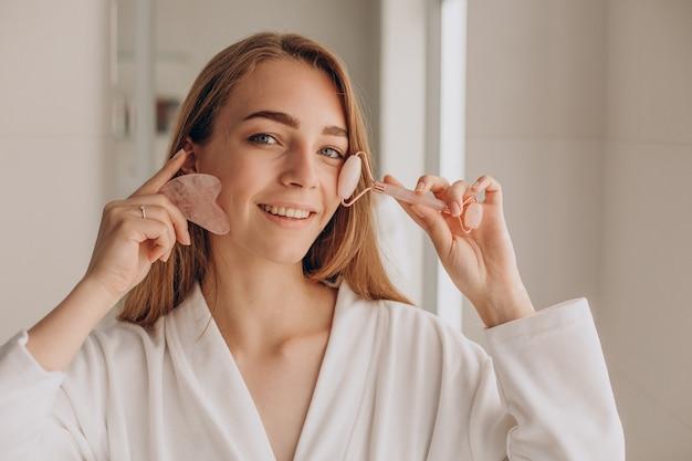Frau macht massage mit gua-sha-stein und gesichtsrolle