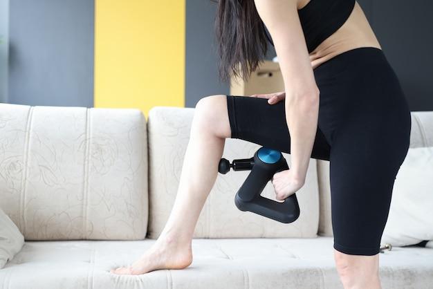 Frau macht massage mit perkussionsmassagegerät des unterschenkels