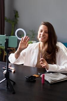Frau macht mit ihrem smartphone einen beauty-vlog