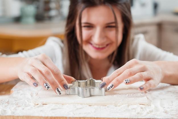 Frau macht mit teigschneider, um einen keks zu machen