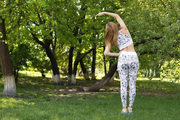 Frau macht morgenübung im park