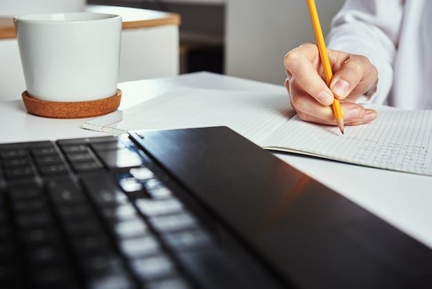 Frau macht notizen im notizbuch und benutzt laptop zum lernen