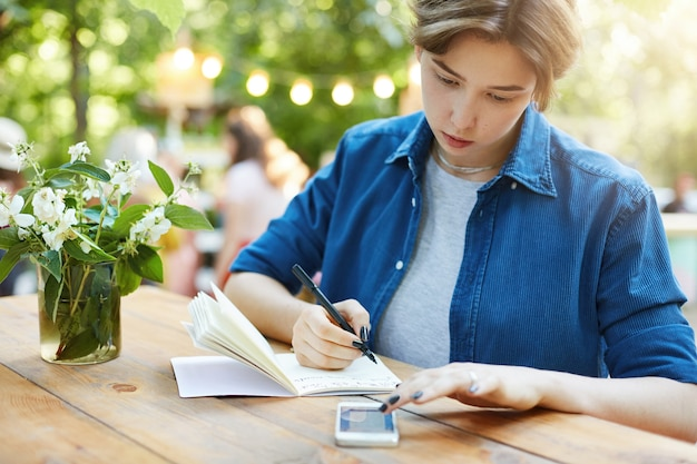 Frau macht notizen mit smartphone. außenporträt einer jungen frau, die in ihrem notizbuch schreibt