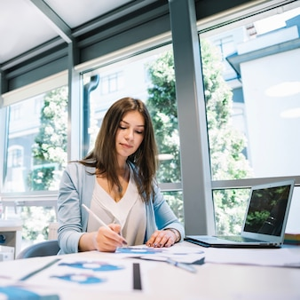 Frau macht papierkram am laptop