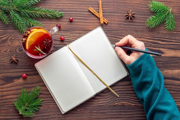 Frau macht pläne für weihnachtsferien im notizblock aus papier am holztisch, während sie würzigen roten tee trinkt