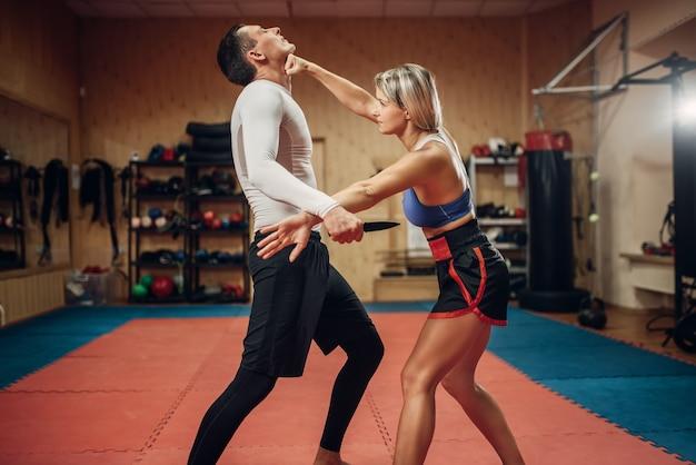 Frau macht schlag in die kehle, selbstverteidigungstraining mit männlichem personal trainer, fitnessstudio interieur. weibliche person auf training, selbstverteidigungspraxis