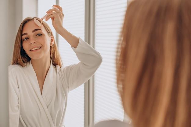 Frau macht selbstmassage mit rosenquarz-gesichtsrolle