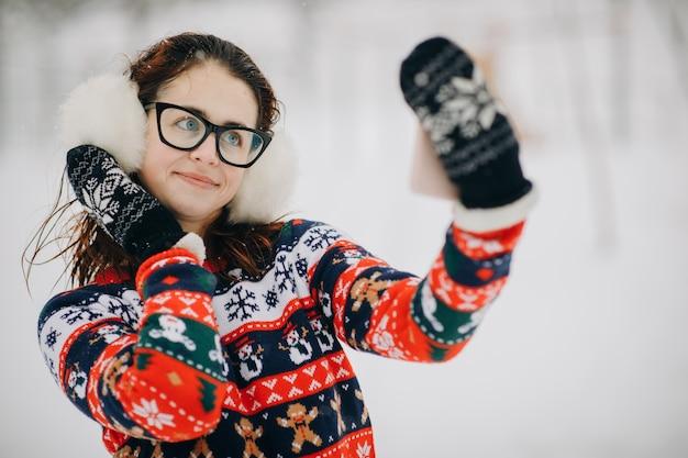 Frau macht selfie im winterpark. lächelndes mädchen macht selfie auf schneebedeckten bäumen in einem winterpark