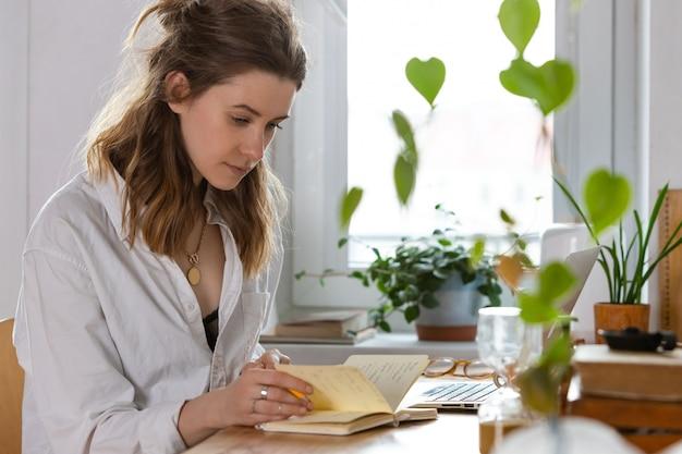 Frau macht sich notizen im notizbuch