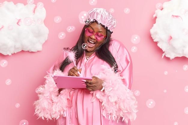 Frau macht sich notizen ins tagebuch genießt häusliche atmosphäre trägt badehut morgenmantel sonnenbrille lächelt fröhlich posiert auf rosa