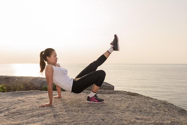 Frau macht sport im freien am strand. fitness- und lifestyle-konzept